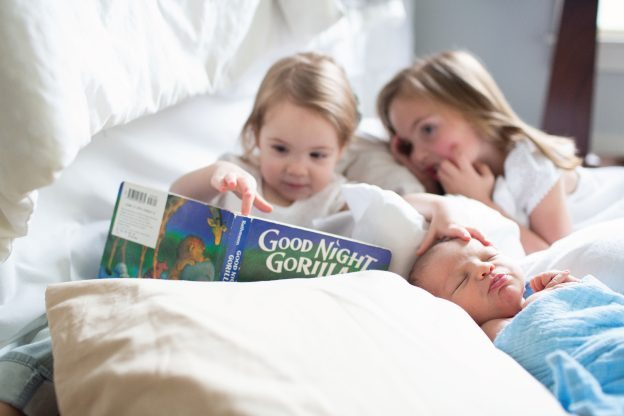 siblings reading to new baby