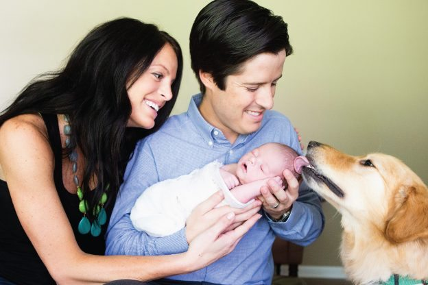couple with dog licking new baby