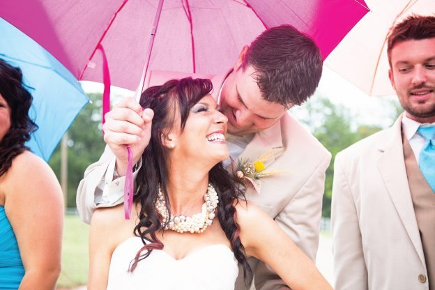 Smiling couple under pink umbrella