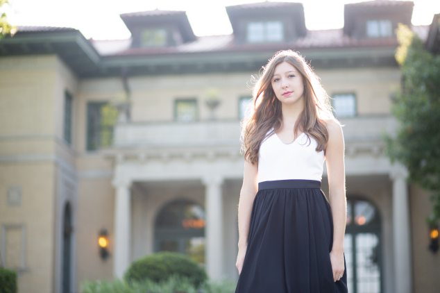 girl in black and white dress in front of mansion