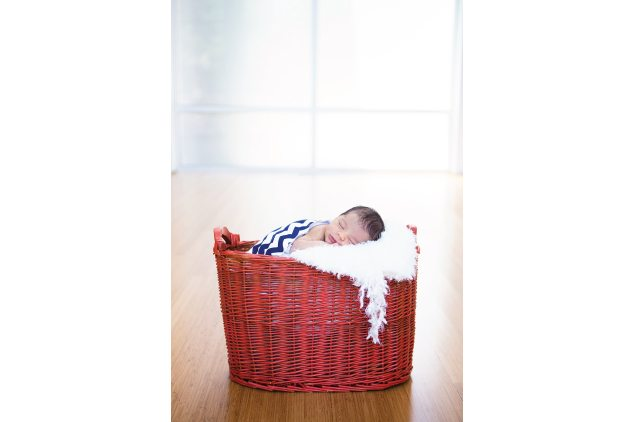 newborn in red basket