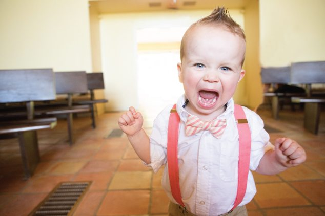 baby in suspenders with mouth open