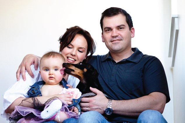 family with dog licking baby