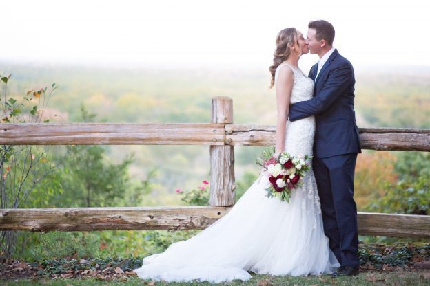 Wedding kiss in front of fence