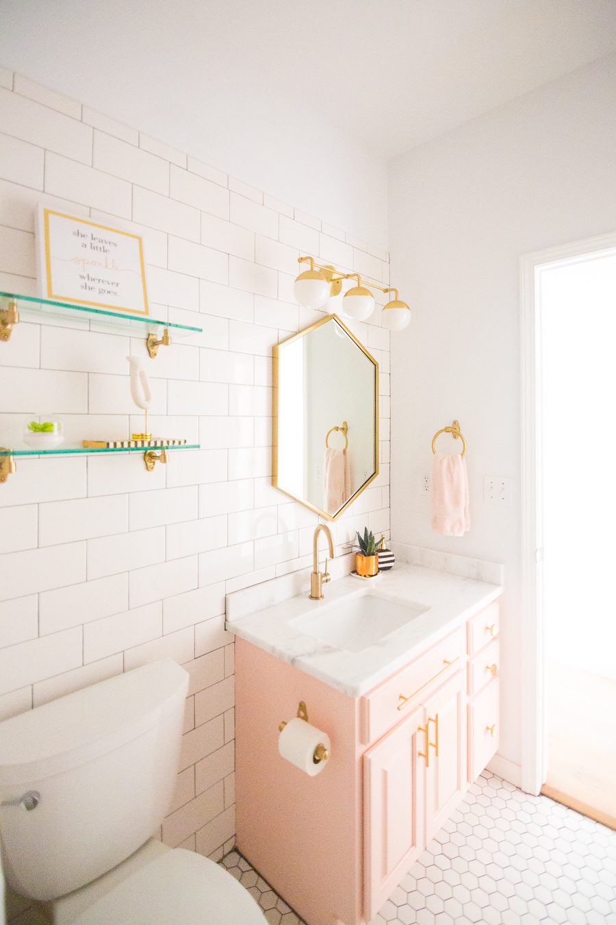 Modern Glam Blush Girls Bathroom Design gold hexagon mirror blush cabinets gold hardware white hexagon floor glass shelves pink bathroom cabinets gold orb sconce-1-2