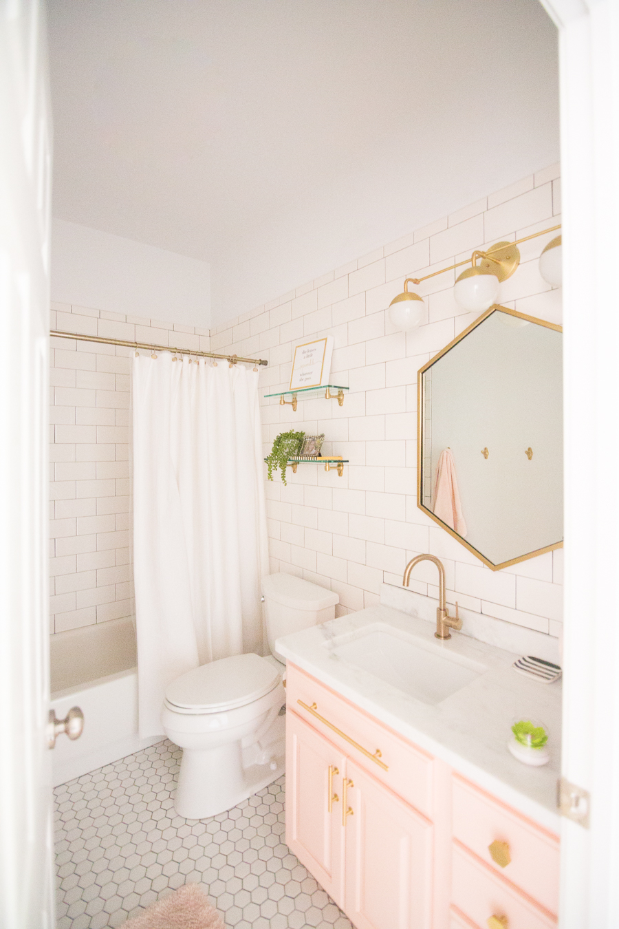 Modern Glam Blush Girls Bathroom Design Gold Hexagon Mirror Blush Cabinets Gold Hardware White Hexagon Floor Glass Shelves Pink Bathroom Cabinets Gold Orb Sconce 4 3 Cc Mike