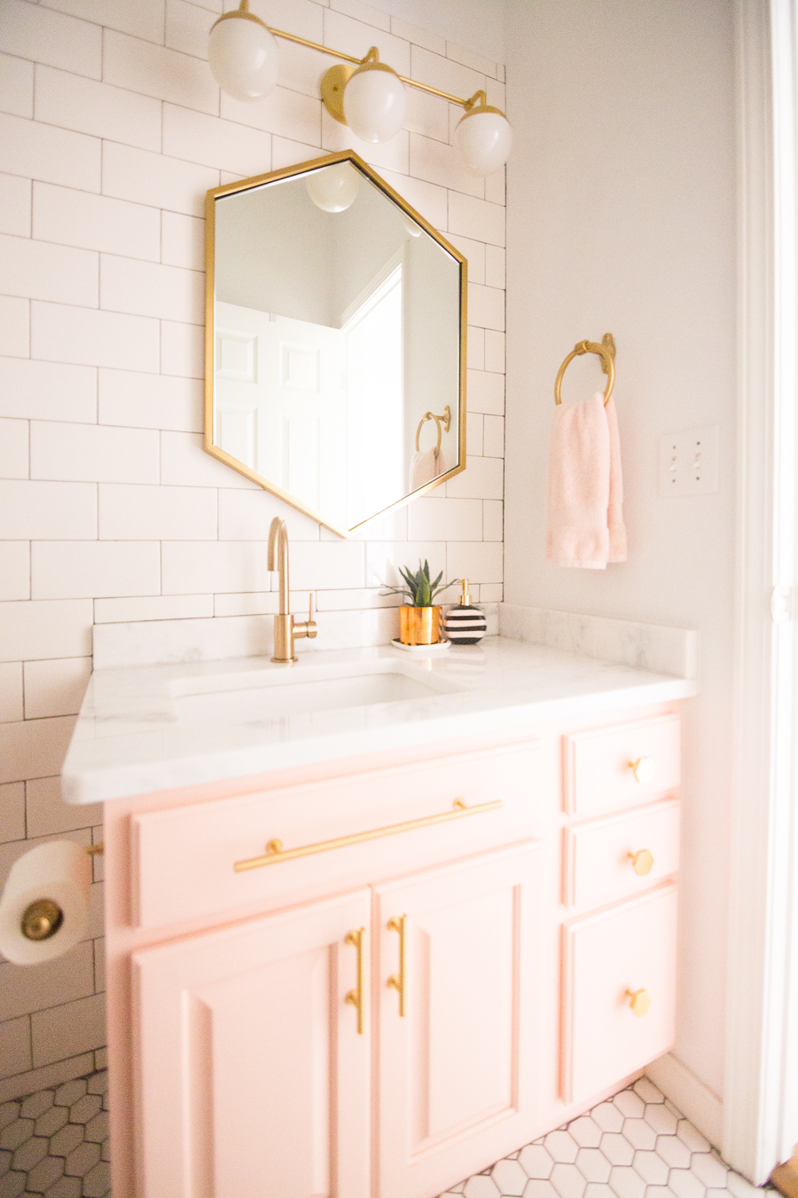 Modern Glam Blush Girls Bathroom Design gold hexagon mirror blush cabinets gold hardware white hexagon floor glass shelves pink bathroom cabinets gold orb sconce-1-3