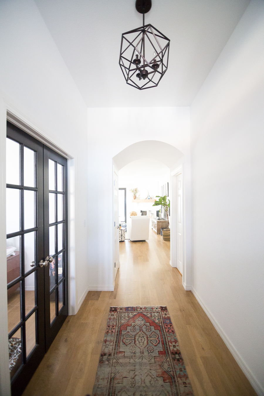 Tulsa Remodel Reveal Modern White Farmhouse black windows and doors kilim rug entryway black hexagon foyer light-1