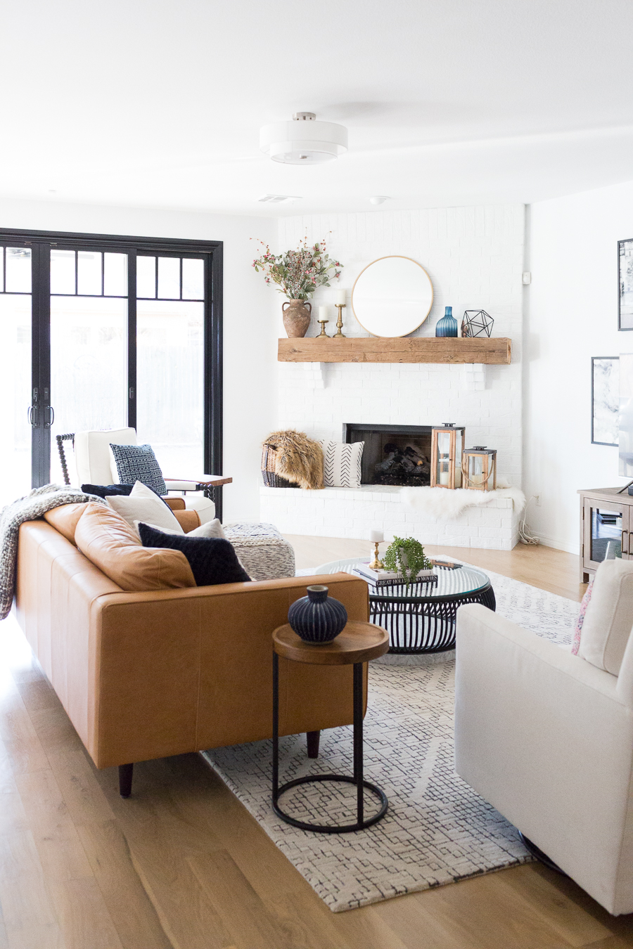 Tulsa Remodel Reveal Modern White Farmhouse black windows and doors modern leather sofa article sven sofa white brick fireplace wood beam mantle tv gallery wall-1