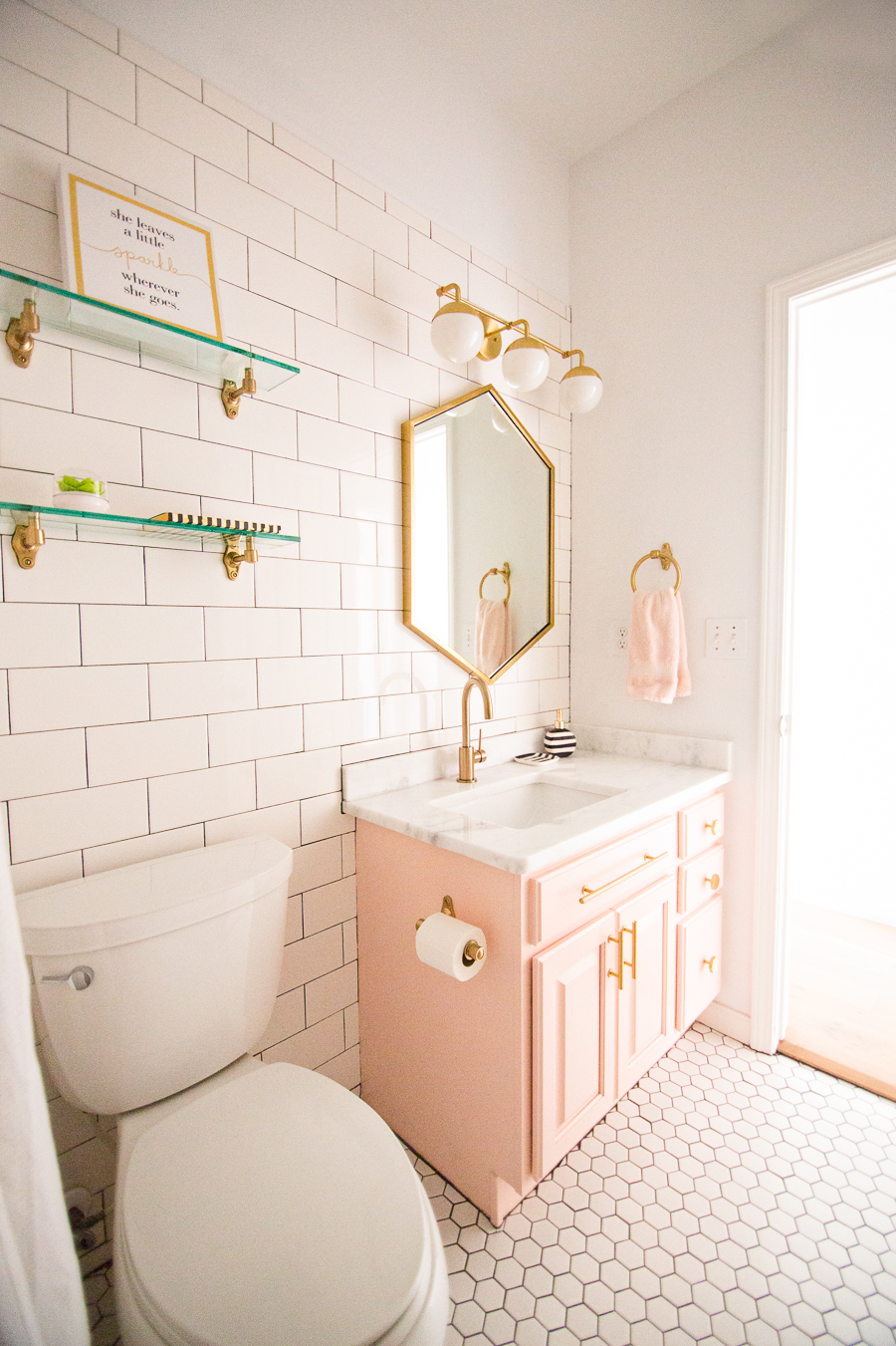 Tulsa Remodel Reveal Modern White Farmhouse modern glam pink girls bathroom gold hexagon mirror blush cabinet gold hardware white hexagon floors glass floating shelves-1