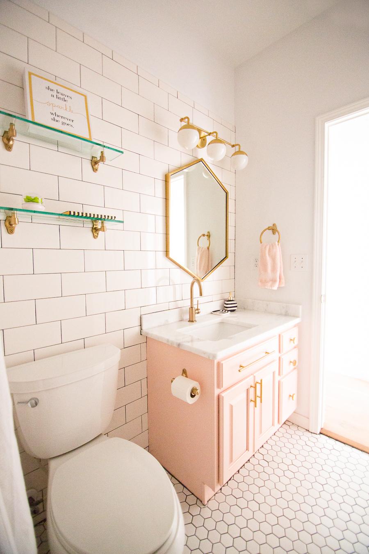 Tulsa Remodel Reveal Modern White Farmhouse modern glam pink girls bathroom gold hexagon mirror blush cabinet gold hardware white hexagon floors glass floating shelves-1