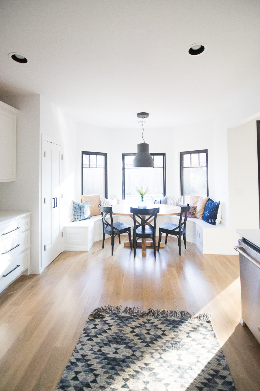 Tulsa Remodel Reveal Modern White Farmhouse with Black WIndows and Doors built in banquette window seat black pendant dining room-1
