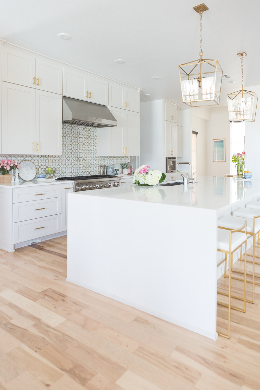 Home and Fashion Memorial Day Sales Weekend gold kitchen lanterns affordable gold bar stools large kitchen island quartz waterfall countertops gold hardware white kitchen cabinets patterned backsplash white kitchen
