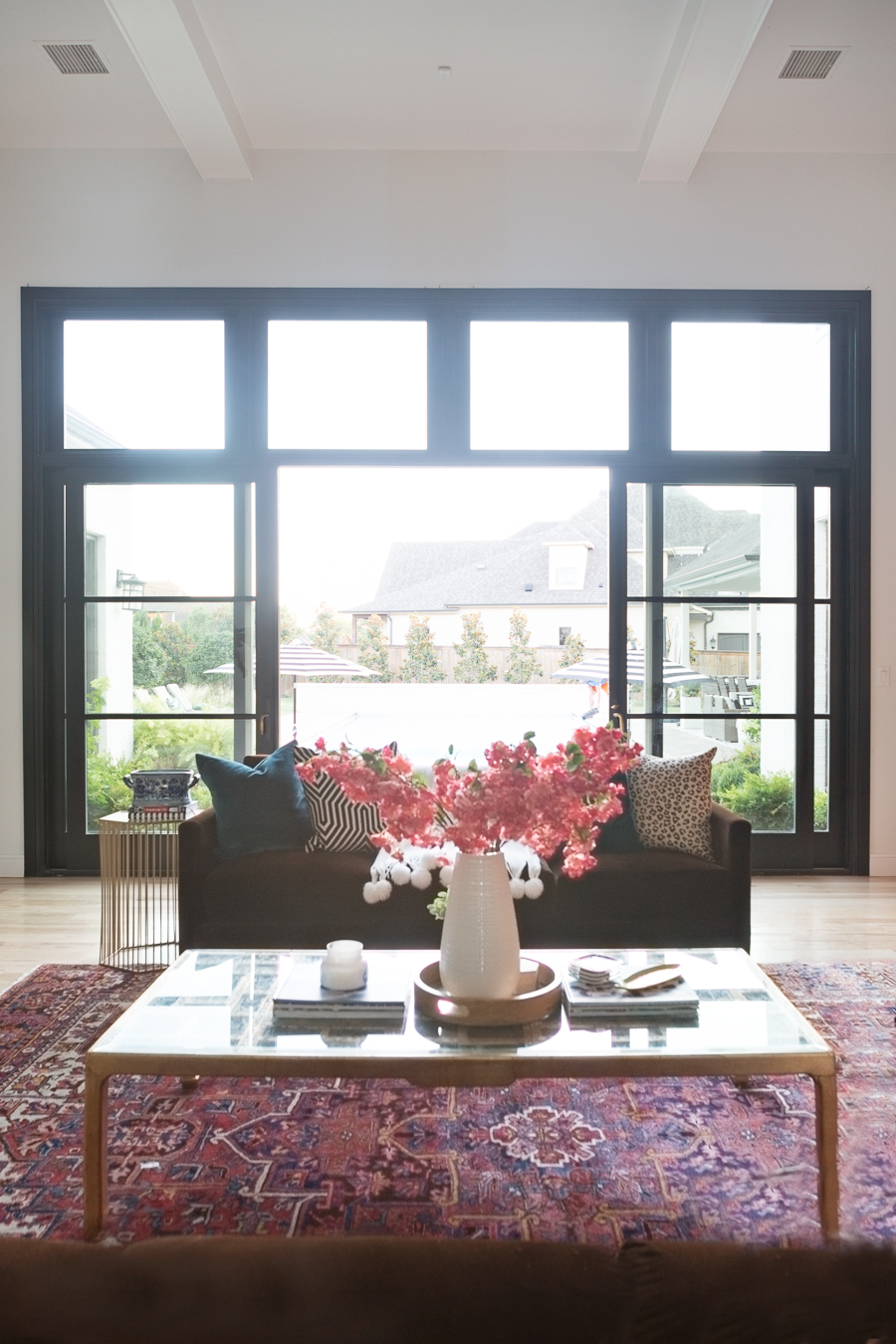 How to Find Black Windows and Doors for Less black windows and doors aluminum clad sliding doors white walls black window beautiful white home pink faux stems black and white graphic pillows leopard pillows gold coffee table pink stems