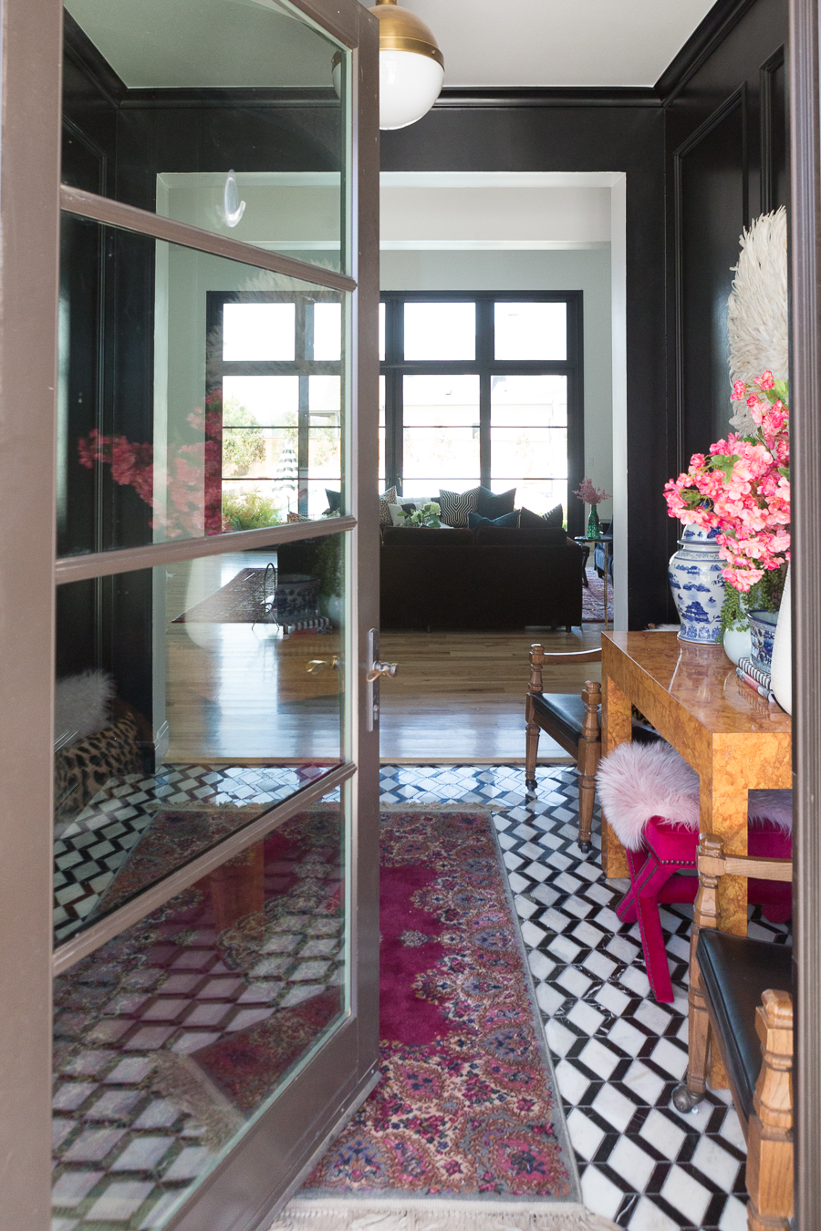 How to Find Black Windows and Doors for Less black and white marble floors in an entryway with black high gloss wood paneling gold visual comfort hick pendant white walls with black windows in the living room