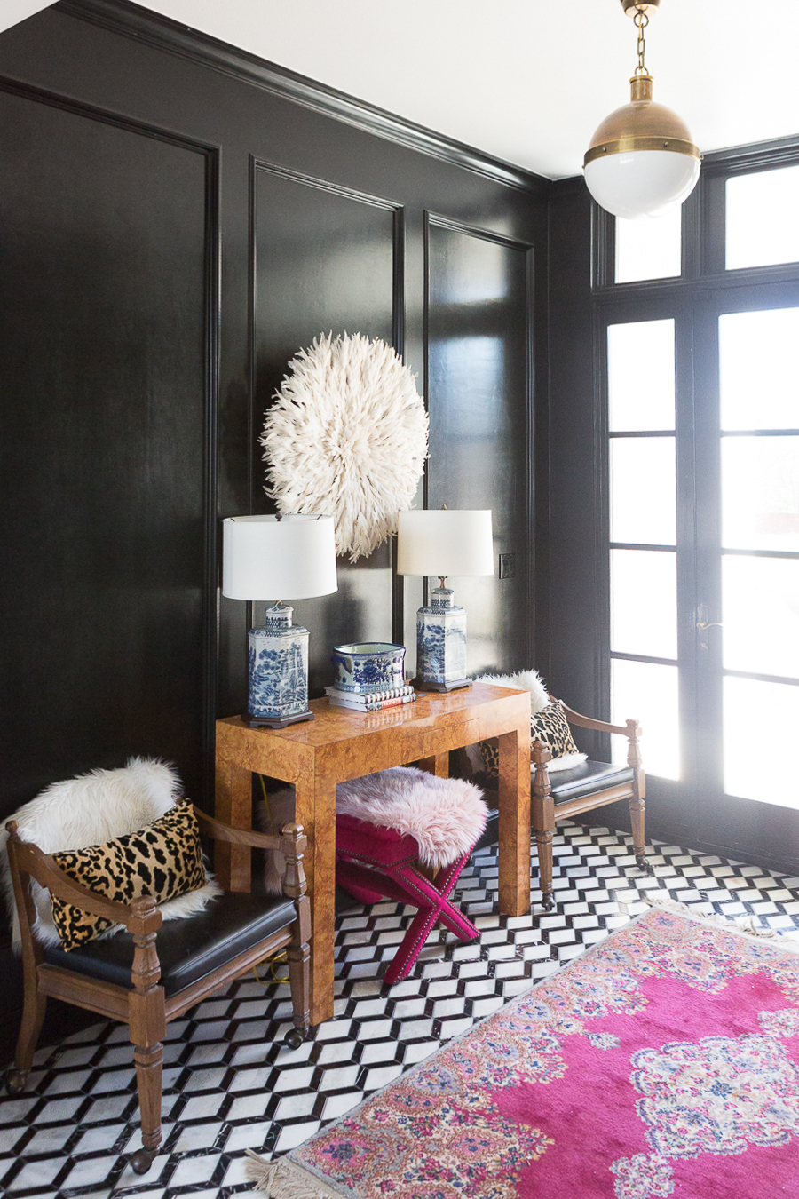 ALUMINUM CLAD Affordable alternatives to steel windows and doors black and white patterned marble floors in a small entryway with a patterned pink vintage rug and a burl wood console with a juju hat hanging above it and a white vase with pink faux stems and paneled wood walls painted high gloss black