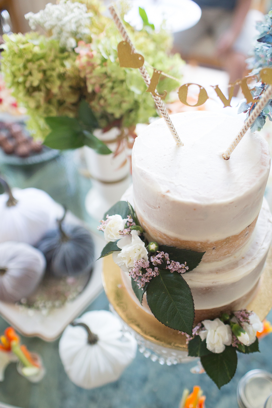 Beautiful Fall Bridal Shower Ideas fall bridal shower cake on a white cake stand surrounded by velvet pumpkins and hydrangeas