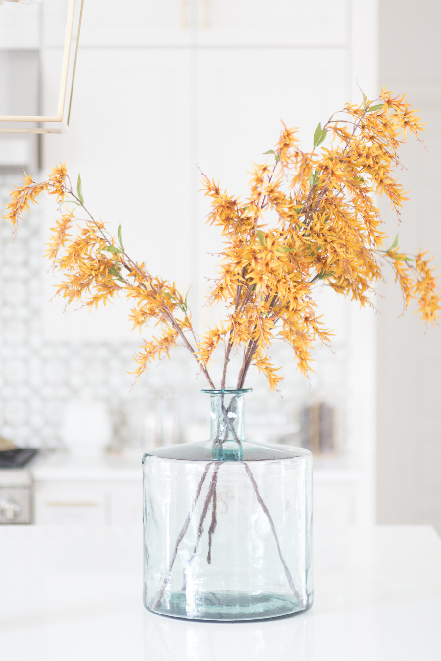 Loveliest Looks of Fall Home Tour Beautiful Fall Home Decor and Fall Fashion Ideas close up photo of yellow faux fall stems in a green vase sitting on a large quartzite waterfall kitchen countertop