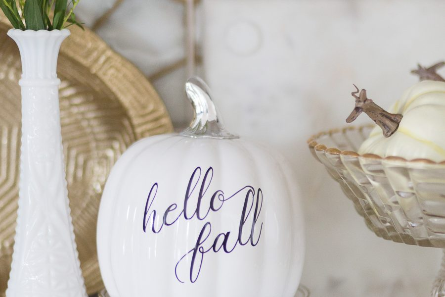 Loveliest Looks of Fall Home Tour Beautiful Fall Home Decor and Fall Fashion Ideas hello fall ceramic white pumpkin sitting on top of white plates with a cake glass dish full of white pumpkins next to it in front of patterned honeycomb ann sacks tile backsplash in a white kitchen
