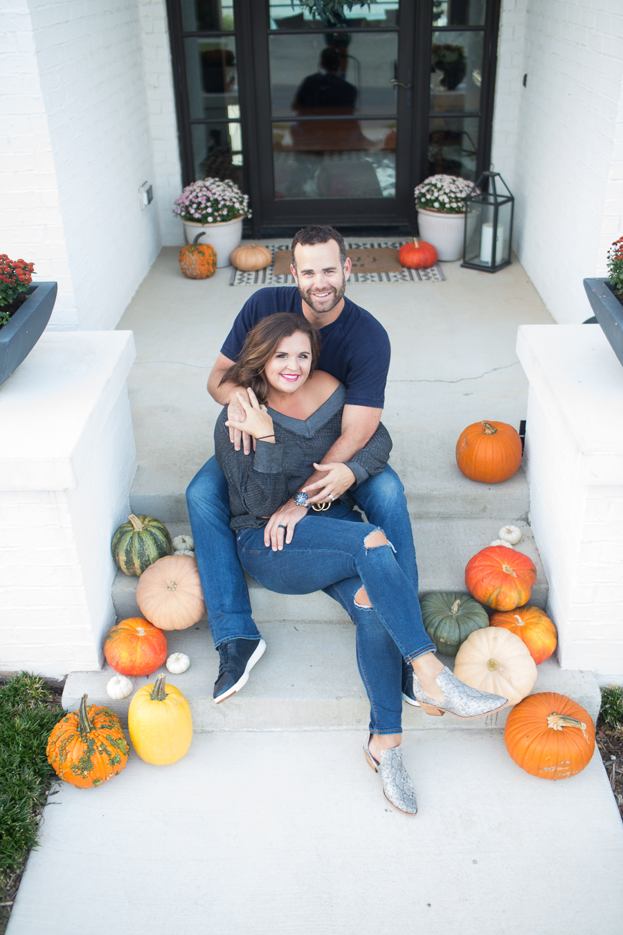 Loveliest Looks of Fall Home Tour Beautiful Fall Home Decor and Fall Fashion Ideas couple who does renovations and design sitting on the front steps of their fall front porch surrounded by pumpkins with the wife wearing old navy rockstar jeans and and off the shoulder gray top and snake skin boots and the husband wearing jeans and a navy shirt and navy cole hahn shoes