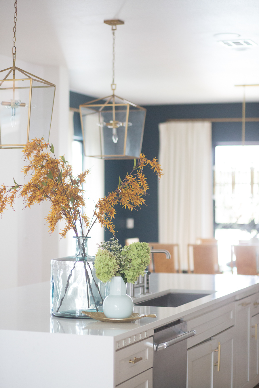 Loveliest Looks of Fall Home Tour Beautiful Fall Home Decor and Fall Fashion Ideas large white quartzite waterfall kitchen island with six gold barstools and a large green vase with yellow faux fall stems sitting on top of the countertop and gold kitchen lanterns hanging above the countertop then white kitchen cabinets with ann sacks patterned backsplash and gold hardware on the cabinets looking into a dark green dining room with a sputnik chandelier and burl wood dining room chairs