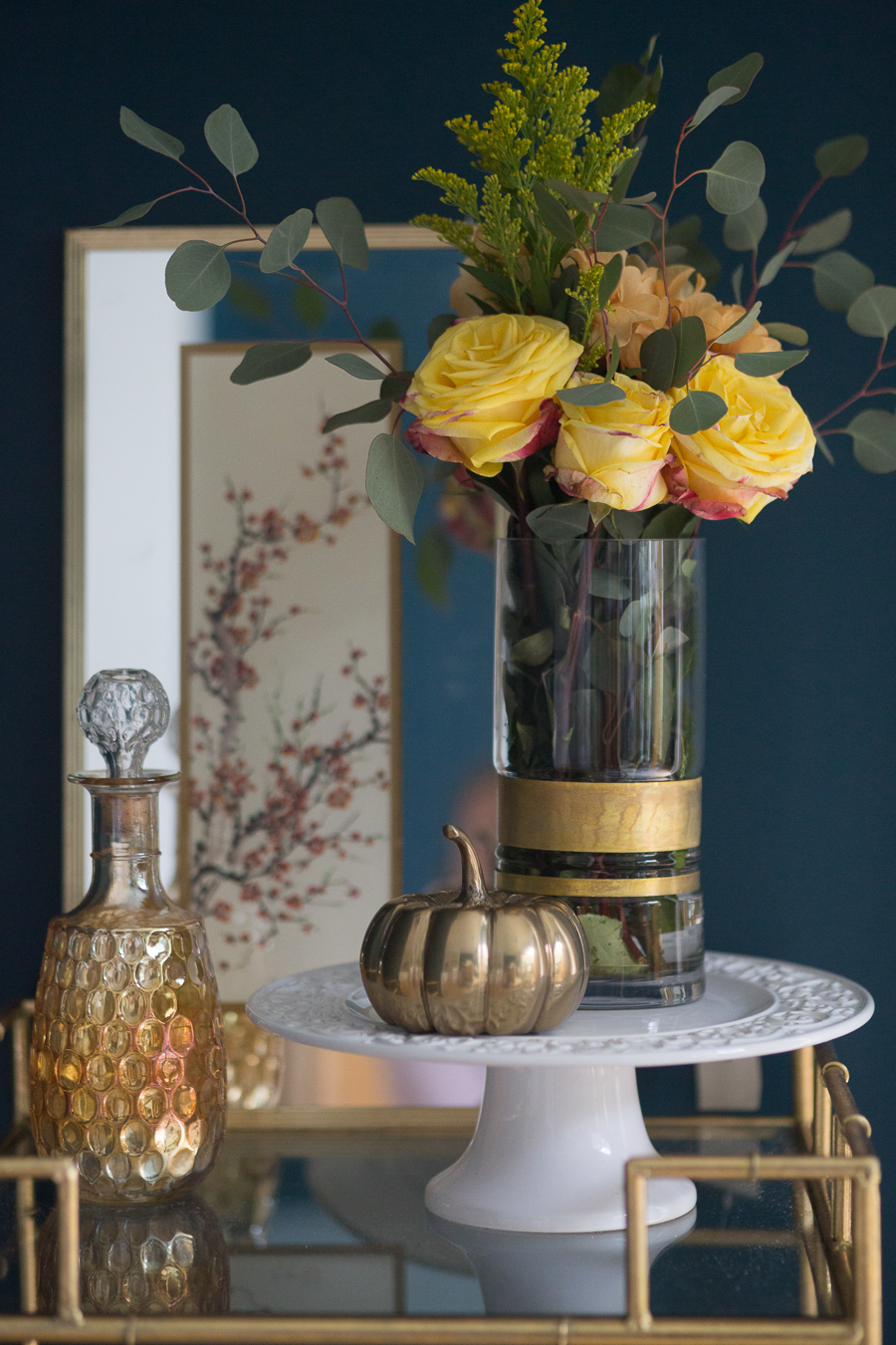 Loveliest Looks of Fall Home Tour Beautiful Fall Home Decor and Fall Fashion Ideas fall bar cart styling gold bar cart in a dark green dining room with a white cake plate and a gold pumpkin sitting on top of it with a clear glass vase with gold detailing around the bottom full of fall colored roses and flowers