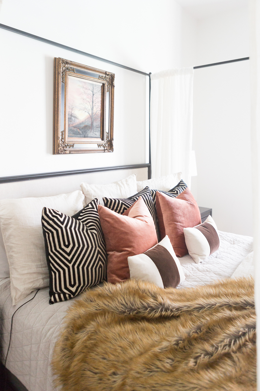 Loveliest Looks of Fall Home Tour Beautiful Fall Home Decor and Fall Fashion Ideas white master bedroom with a black canopy bed and a gold and black frame hanging above the bed with fall tree art linen bedding with black and white graphic mary mcdonald fabric velvet pillows behind blush velvet pillows and a fur throw on the bed
