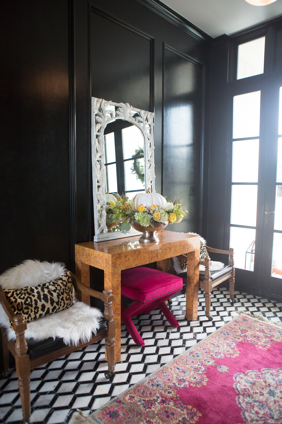 Loveliest Looks of Fall Home Tour Beautiful Fall Home Decor and Fall Fashion Ideas entryway with black paneling painted high gloss and marble black and white floors with a burl wood console table and a white mirror hanging about it and a silver urn floral pumpkin centerpiece sitting on the table