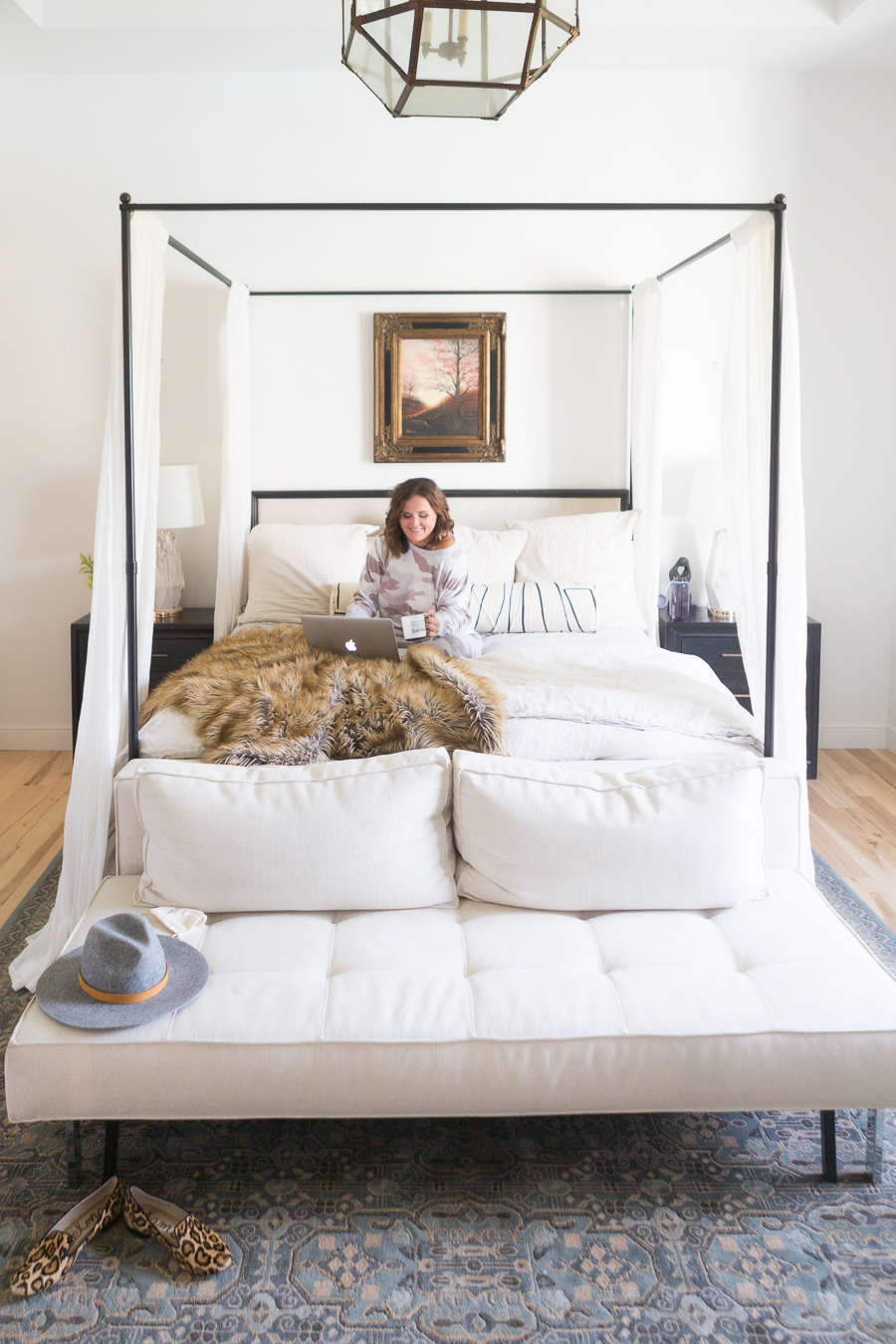 Loveliest Looks of Fall Home Tour Beautiful Fall Home Decor and Fall Fashion Ideas lifestyle blogger in Aerie camo jogger set sitting on a canopy bed with linen bedding and a fur throw with a fall canvas photo of a tree hanging above the bed and a circa caged lantern pendant hanging from the ceiling