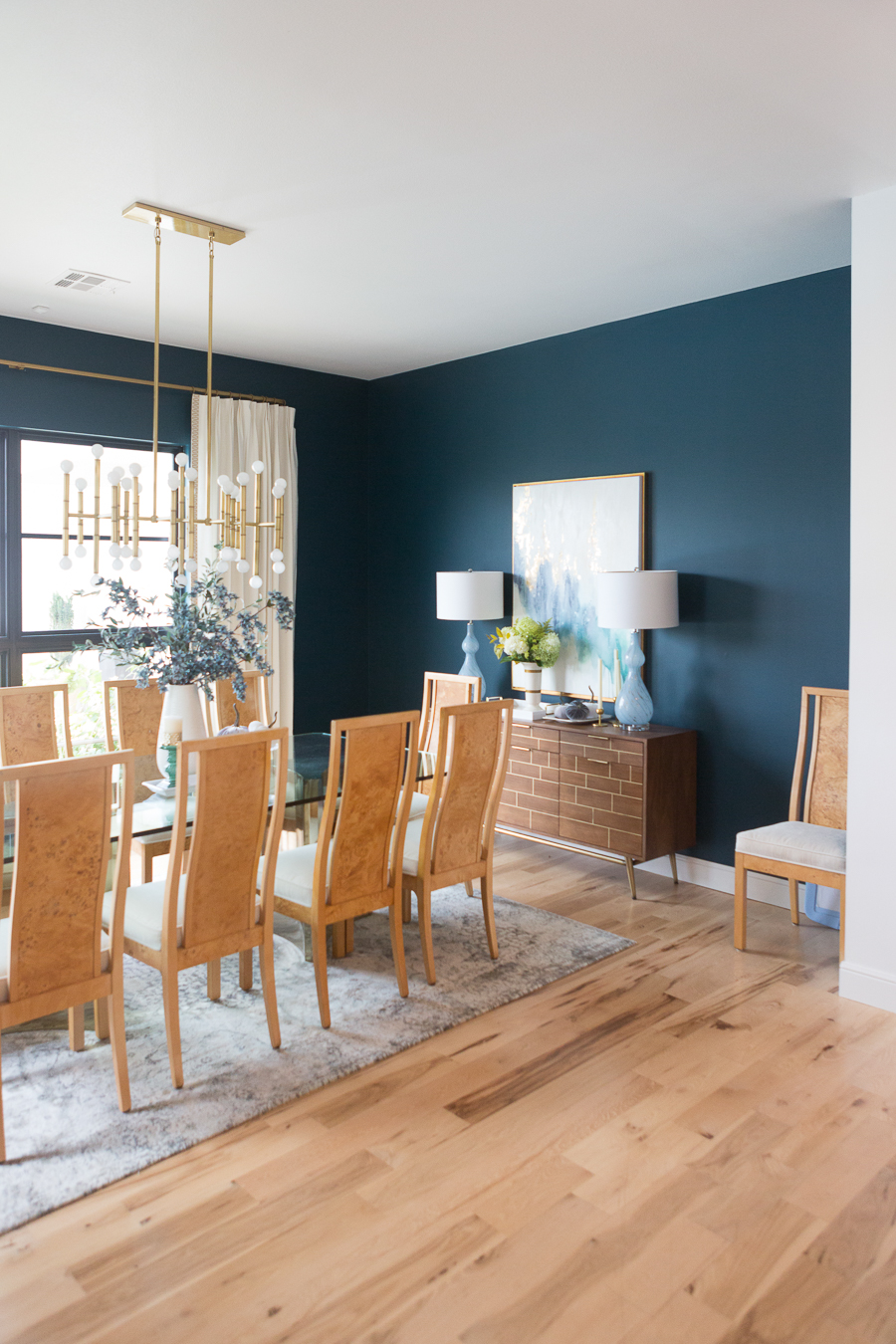 CC and Mike Guide to Buying the Perfect Area Rug jonathan adler sputnik light fixture dark green walls burl wood dining chairs