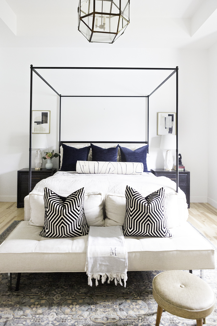 10 Beautiful Minted Fine Art Prints for Home Decor black iron canopy bed with linen bedding navy velvet pillows and a black and white bolster pillow beside the bed black night stands with gold hardware marble lamps with white shades and navy gray and black minted art in a gold frame hanging above the night stands
