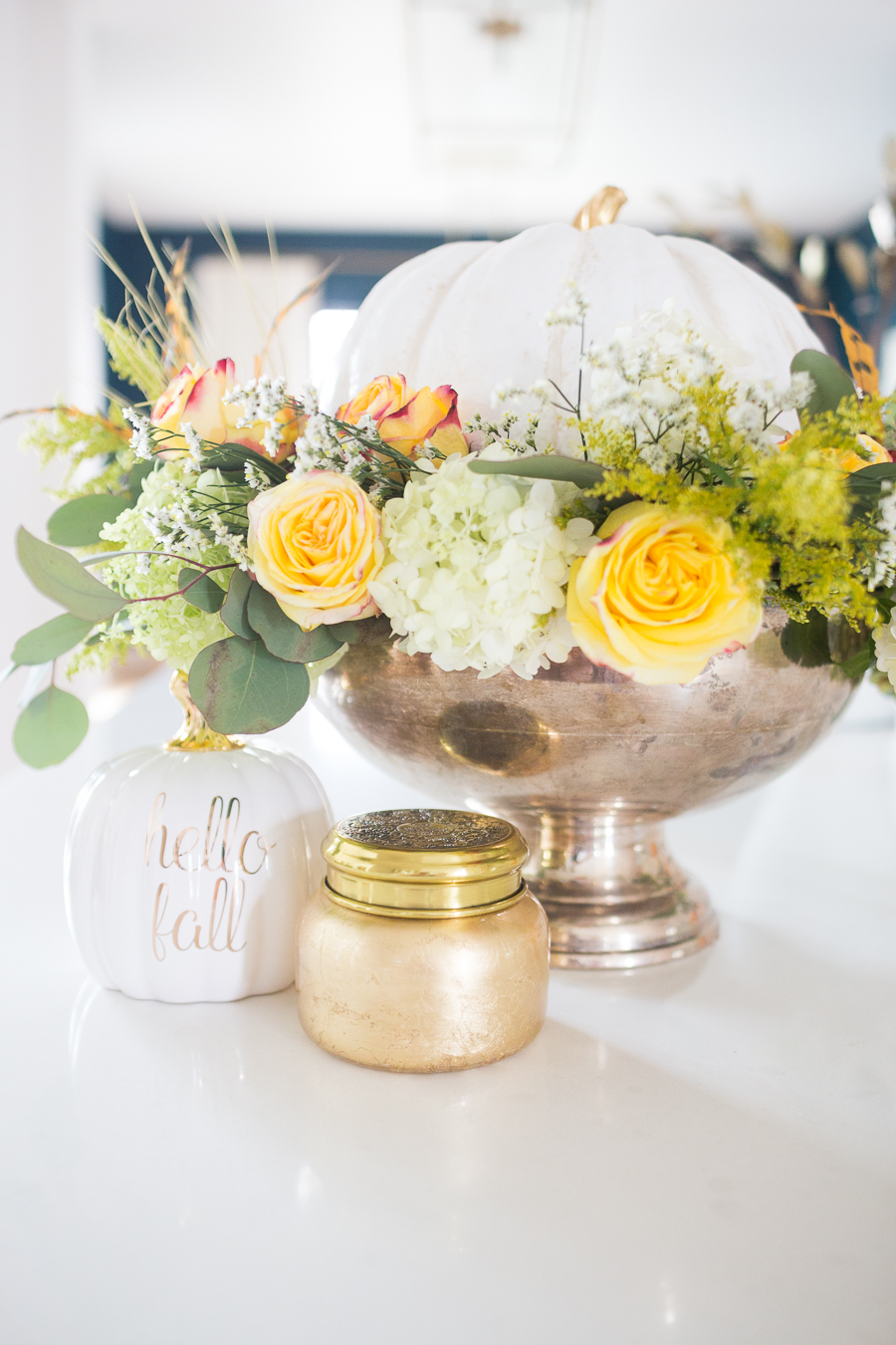 DIY Silver Urn Pumpkin Centerpiece for Fall hydrangeas and eucalyptus and roses inside of a silver urn with a ceramic pumpkin for a Thanksgiving centerpiece sitting beside a fall Anthropologie candle and hello fall pumpkin