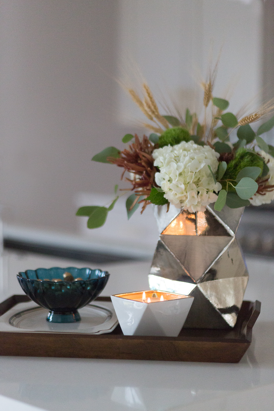 Simple Ways to Decorate for the Holidays from West Elm large wood tray faceted silver vase with hydrangeas and fall flower arrangement scented candle quartz waterfall countertops with gold bar stools