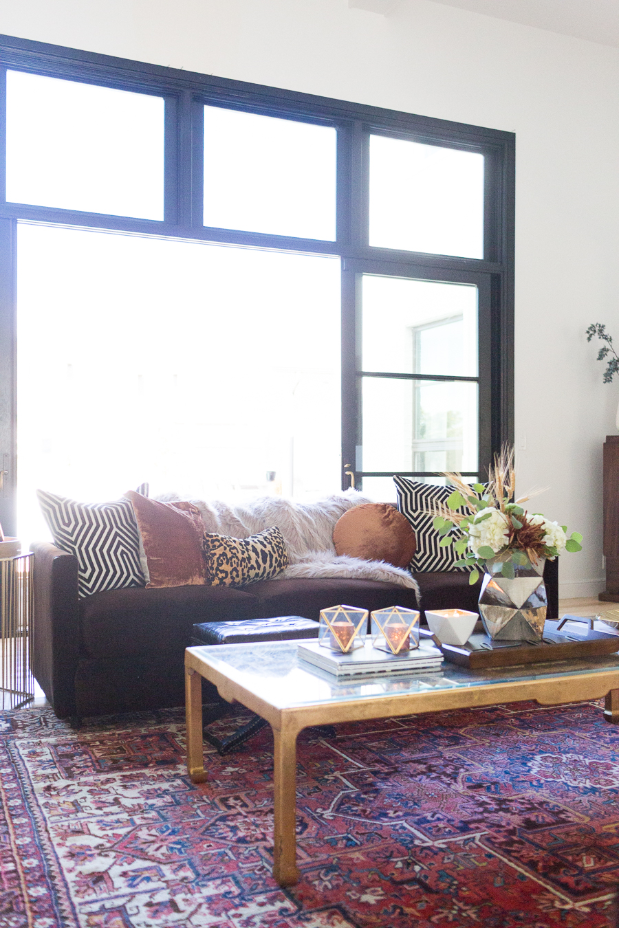 Simple Ways to Decorate for the Holidays from West Elm living room with chocolate velvet couch covered in copper velvet pillows and leopard pillows with a faux fur throw gold coffee table with a wood tray styled for Thanksgiving