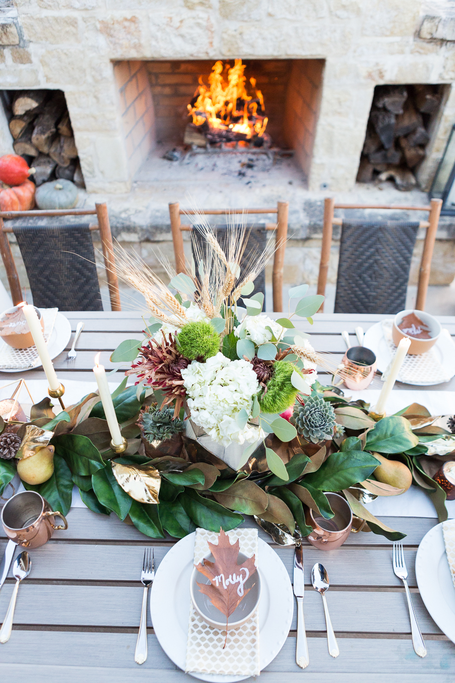Simple Ways to Decorate for the Holidays from West Elm outdoor Friendsgiving and thanksgiving tablescape magnolia garland with gold candlesticks and a rock outdoor fireplace and copper votive candles