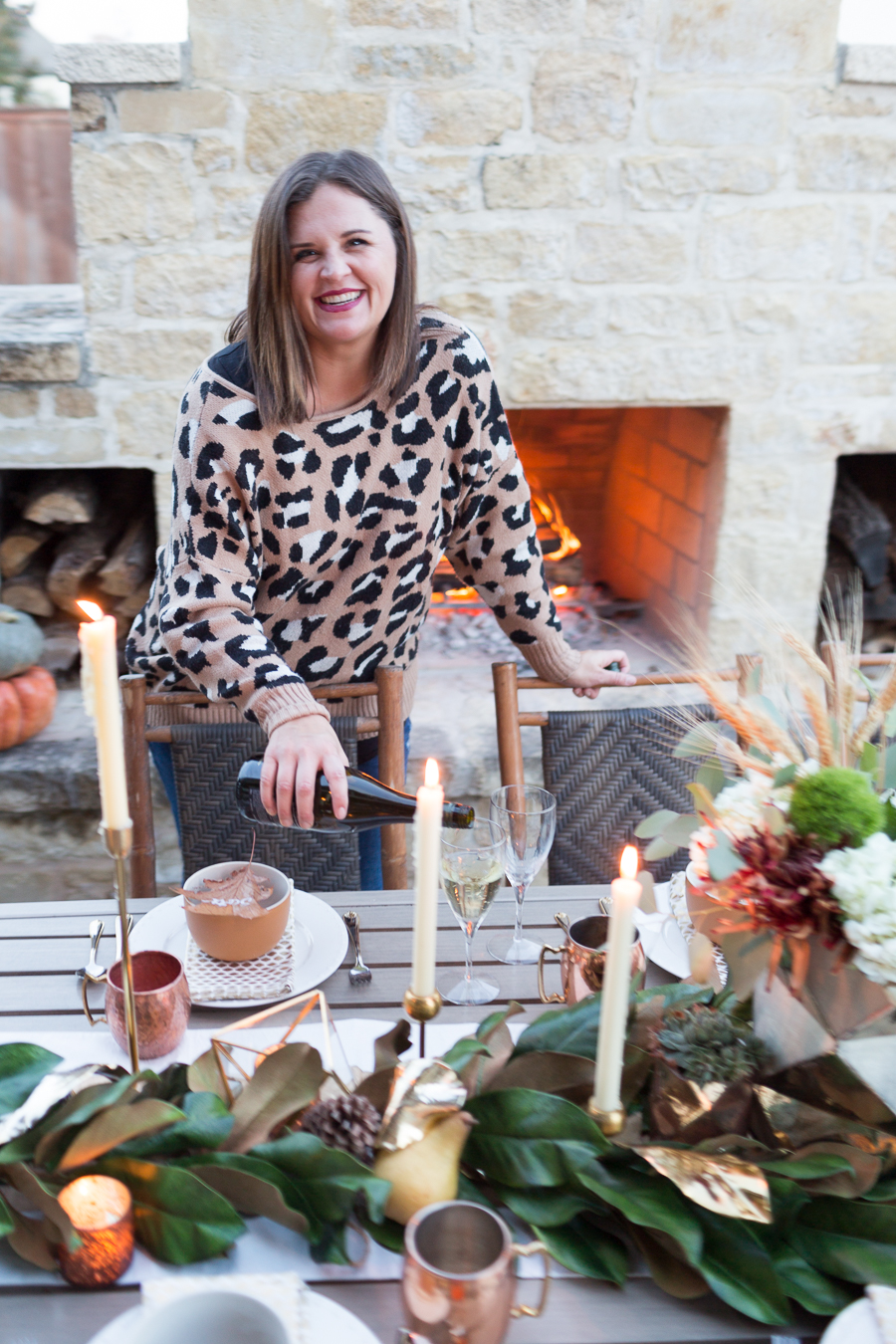 Simple Ways to Decorate for the Holidays from West Elm outdoor Friendsgiving and thanksgiving tablescape magnolia garland with gold candlesticks and a rock outdoor fireplace and copper votive candles hay bail with a chunky knit throw and copper velvet pillows