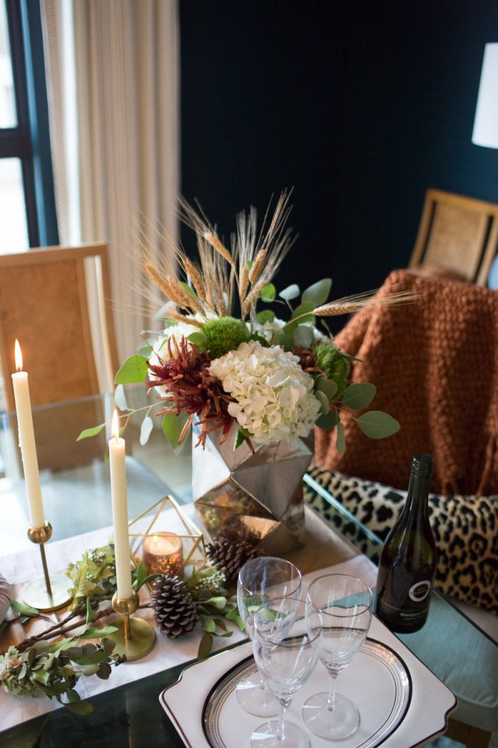 Simple Ways to Decorate for the Holidays from West Elm dark green painted dining room with glass and gold marble dining room table and burl wood chairs with a holiday tablescape with gold candlesticks and a large silver faceted vase with fresh flowers