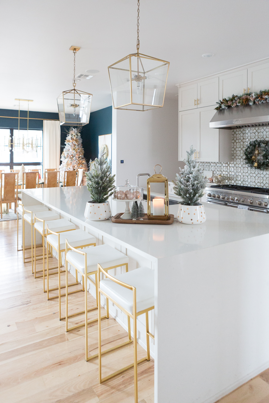 Budget Friendly Holiday Decor from Walmart white quartz waterfall island with gold bar stools and gold lanterns and a wood tray with a gold lantern and flocked Christmas trees in a polka dot vase