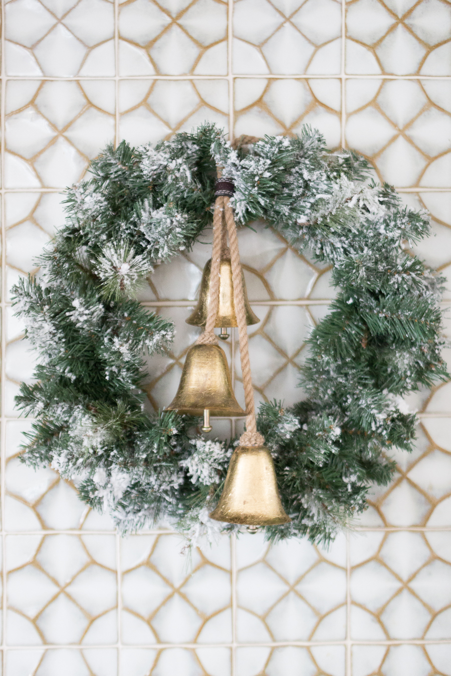 Budget Friendly Holiday Decor from Walmart affordable flocked wreaths with vintage gold bells on ceramic tile backsplash