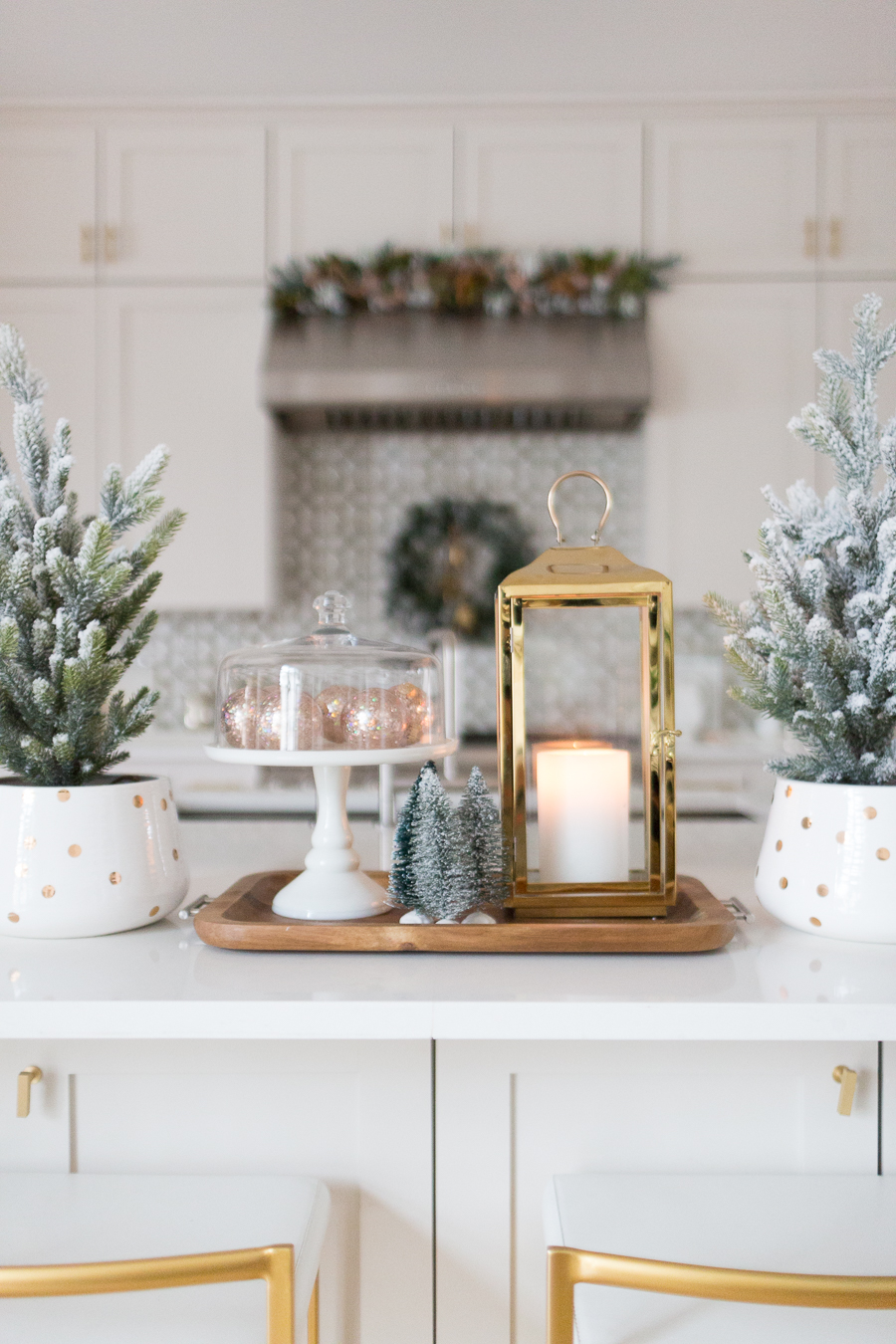 Budget Friendly Holiday Decor from Walmart wood tray with a gold lantern and pioneer woman white cakestand on top of a large quartz waterfall island