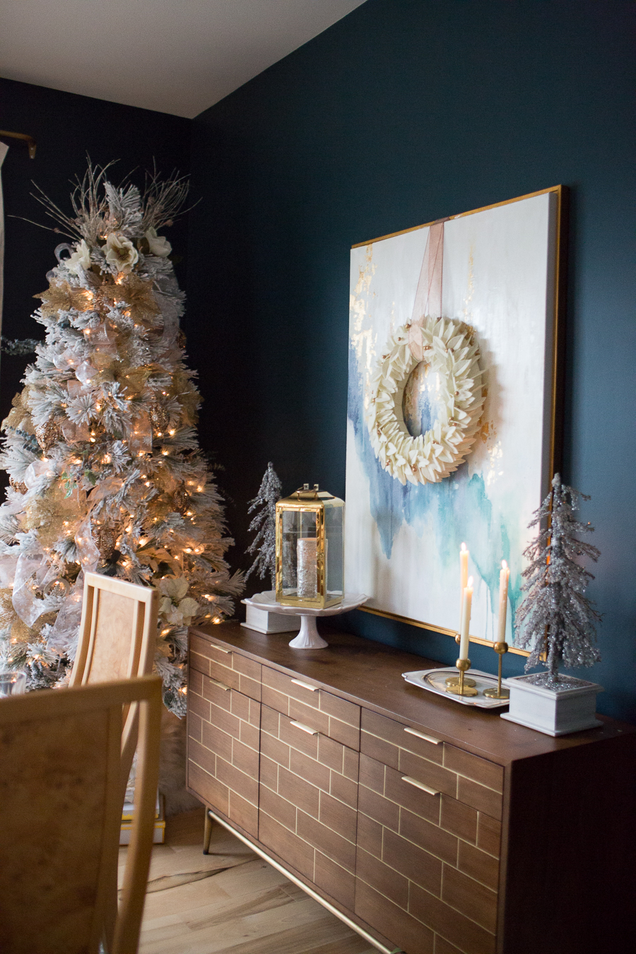Budget Friendly Holiday Decor from Walmart wood tray with a gold lantern and pioneer woman white cakestand on top of a large quartz waterfall island Christmas tree in a dark blue green dining room with an abstract painting hanging on the wall