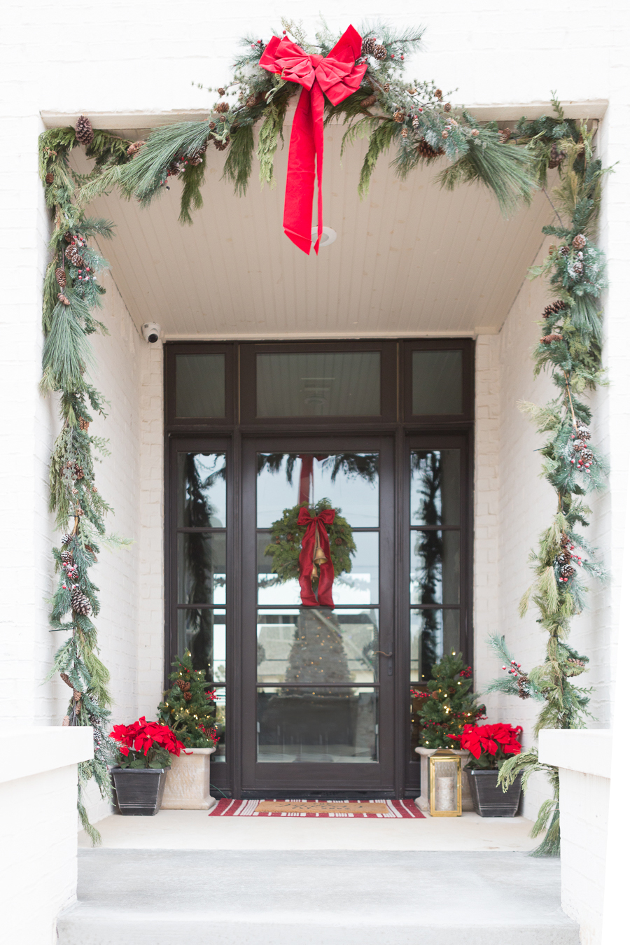 Holiday-Decor-Favorites-from-Home-Depot white brick exterior with fresh Christmas garland and red bows Christmas wreath with gold bells and a red bow silk poinsettias in a copper pot on a front porch black glass front door