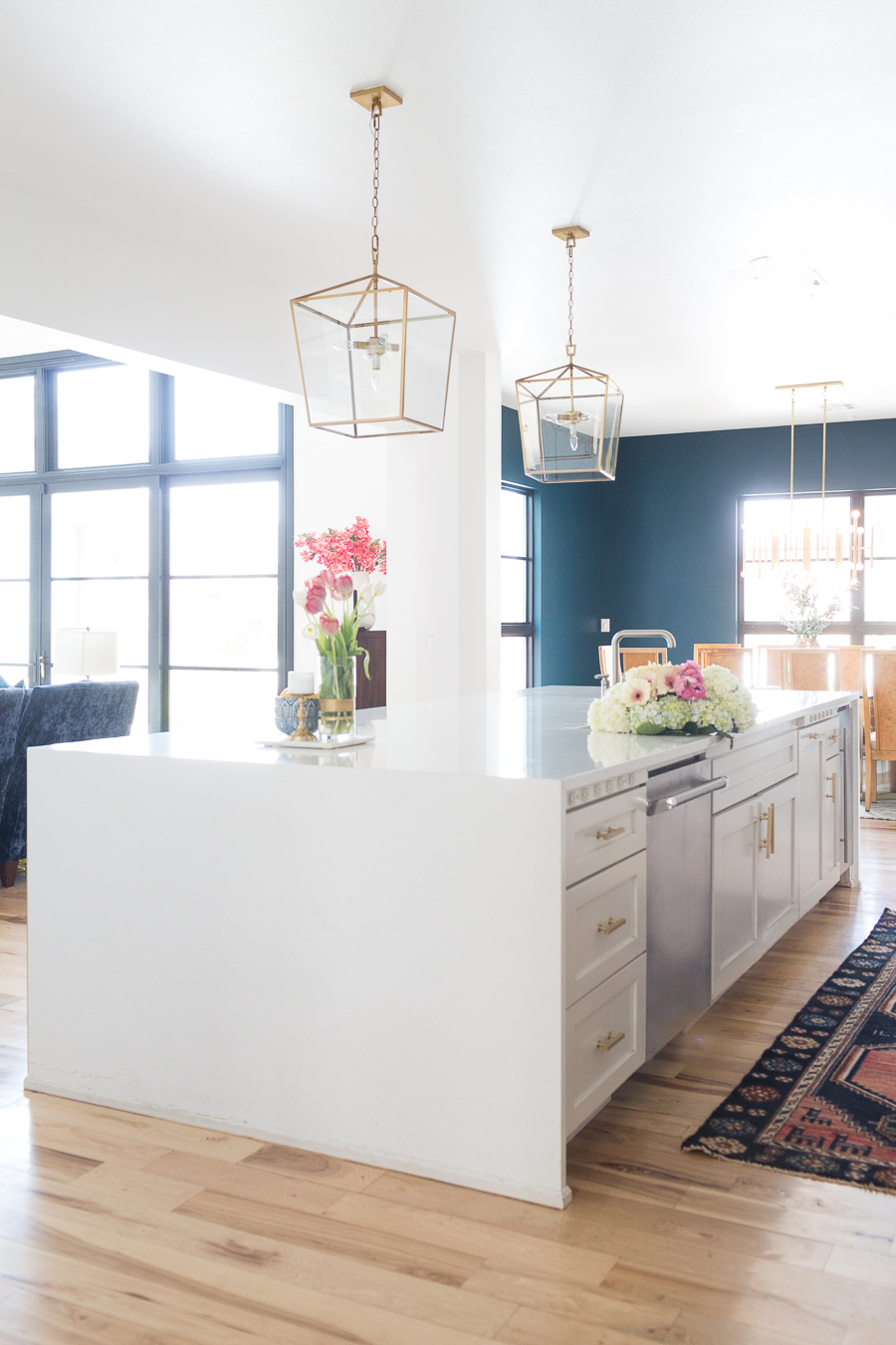 How to Find Black Windows and Doors for Less large waterfall kitchen island with quartz countertops and gold kitchen pendants with dark blue green dining room and white walls with black windows and doors