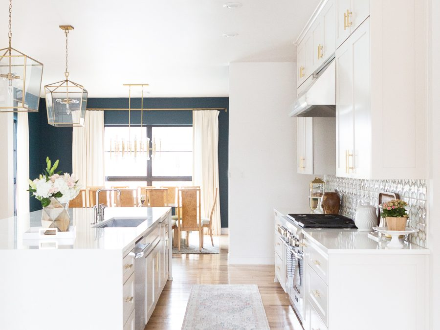 10 Beautiful Kitchen Runners for Your Home white kitchen with faded blue kitchen runner and golden light fixtures