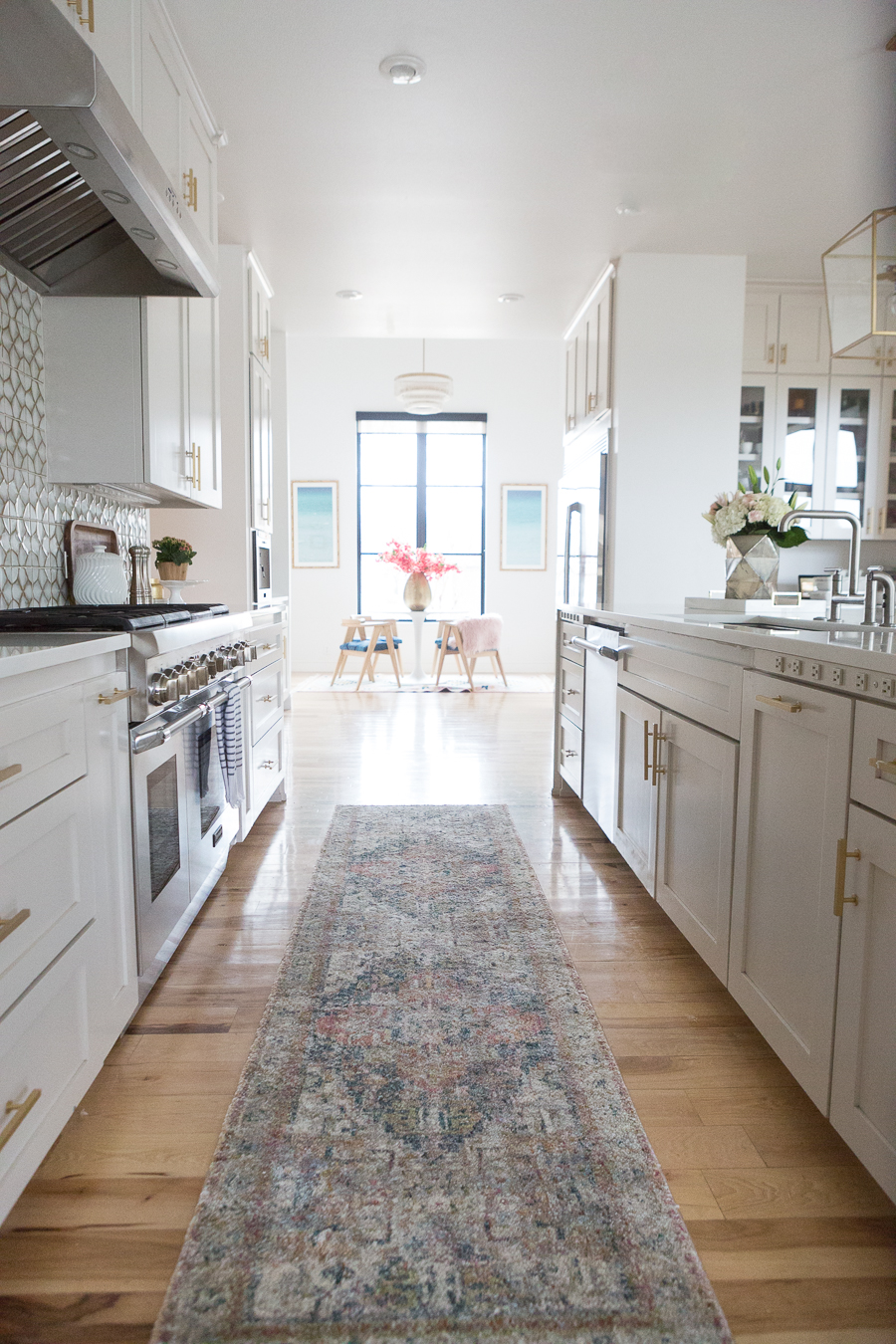 10 Beautiful Kitchen Runners for Your Home kitchen multi-colored kitchen runner between white cabinets on light wooden floors looking towards kitchen nook