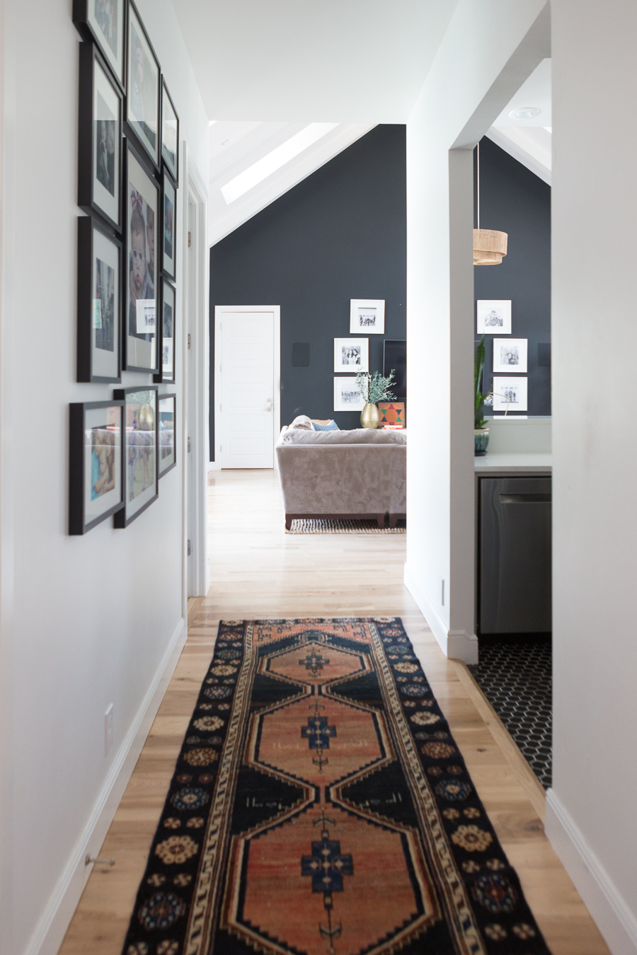 TEEN HANGOUT ROOM DESIGN PLAN AND HANGING CHAIRS looking down the hallway with a dark colored runner and wall art