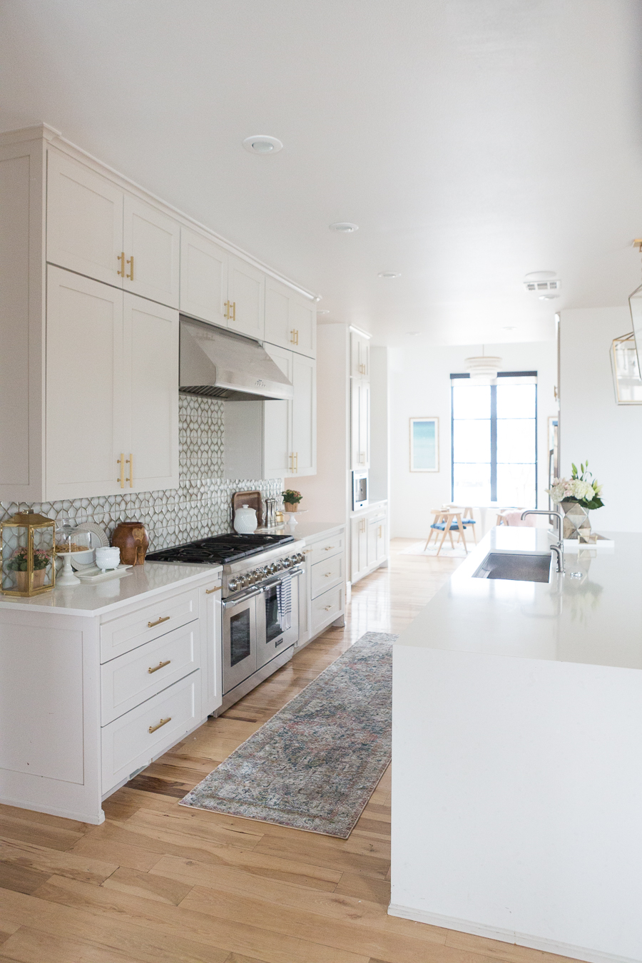 10 Beautiful Kitchen Runners for Your Home wooden floors in white kitchen with white cabinets and countertops with a geometric backsplash and golden accents