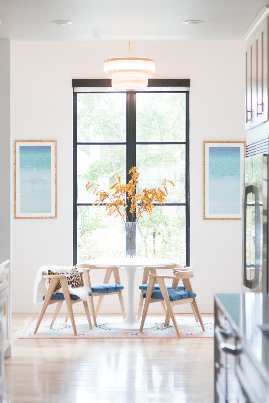 HOW TO FIND BLACK WINDOWS AND DOORS FOR LESS featured in the breakfast nook with natural wood chairs and original prints on the wall