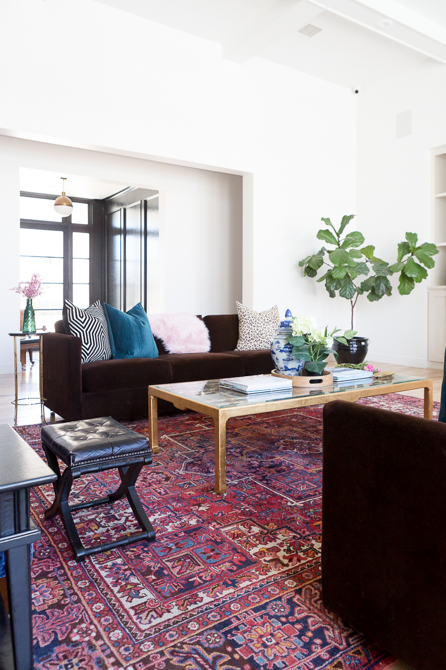 HOW TO FIND BLACK WINDOWS AND DOORS FOR LESS surrounding the front door and leading into eclectic living room with a vintage rug and fig leaf tree