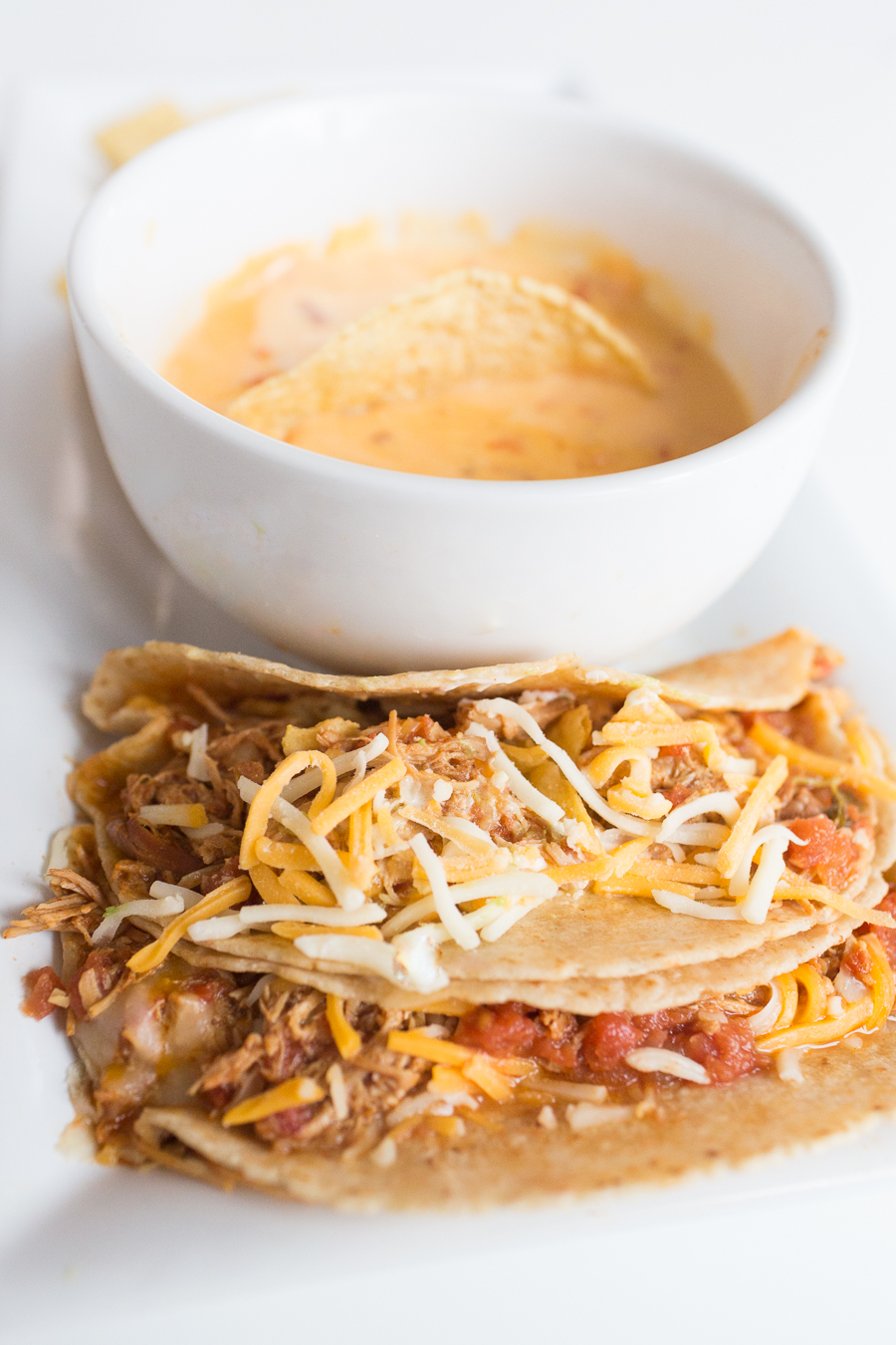 Two Minute Crockpot Chicken Ranch Tacos-1 soft tacos on a long white plate with a bowl of queso and chips
